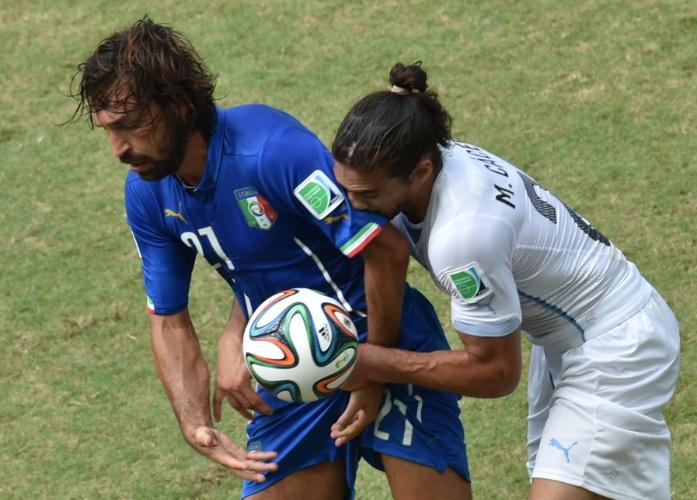 Andrea Pirlo, da Itália, tenta impedir Martin Caceres, do Uruguai, de repor bola em jogo na Arena das Dunas