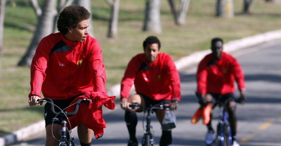 Axel Witsel (esq.) Nacer Chadli e Divock Origi (dir.) pedalam de bicicleta rumo ao treino da Bélgica, em Mogi das Cruzes