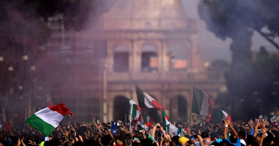 Com Coliseu ao fundo, torcedores italianos agitam bandeiras durante transmissão da partida contra o Uruguai na Piazza Venezia