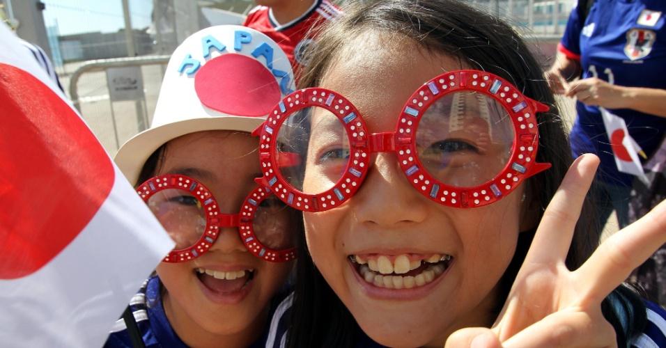 24.jun.2014 - Crianças japonesas brincam com a câmera do lado de fora da Arena Pantanal, antes do jogo contra a Colômbia