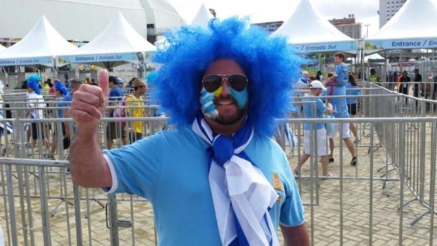 De peruca azul, torcedor uruguaio faz sinal de positivo antes de partida entre Itália x Uruguai, na Arena das Dunas