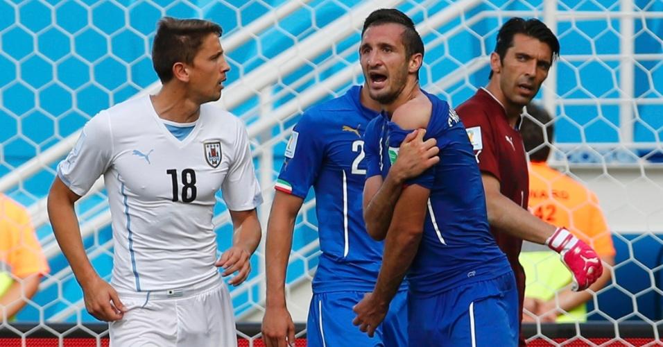 Giorgio Chiellini, da Itália, reclama ter sido mordido por Luis Suarez, do Uruguai, em jogo na Arena das Dunas