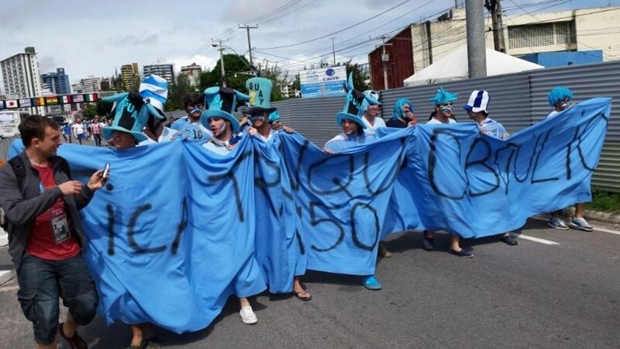 """Grupo de torcedores uruguaios chega ao entorno da Arena das Dunas, em Natal, carregando faixa """"Fica tranquilo Obdúlio 1950"""""""