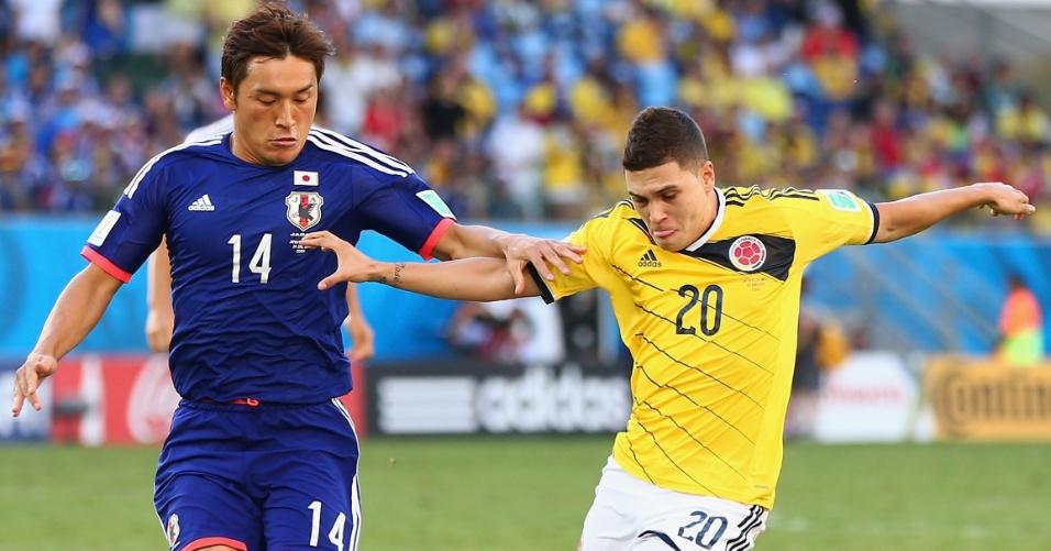 24.jun.2014 - Juan Fernando Quintero, da Colômbia, encara a marcação de Toshihiro Aoyama, do Japão, na Arena Pantanal