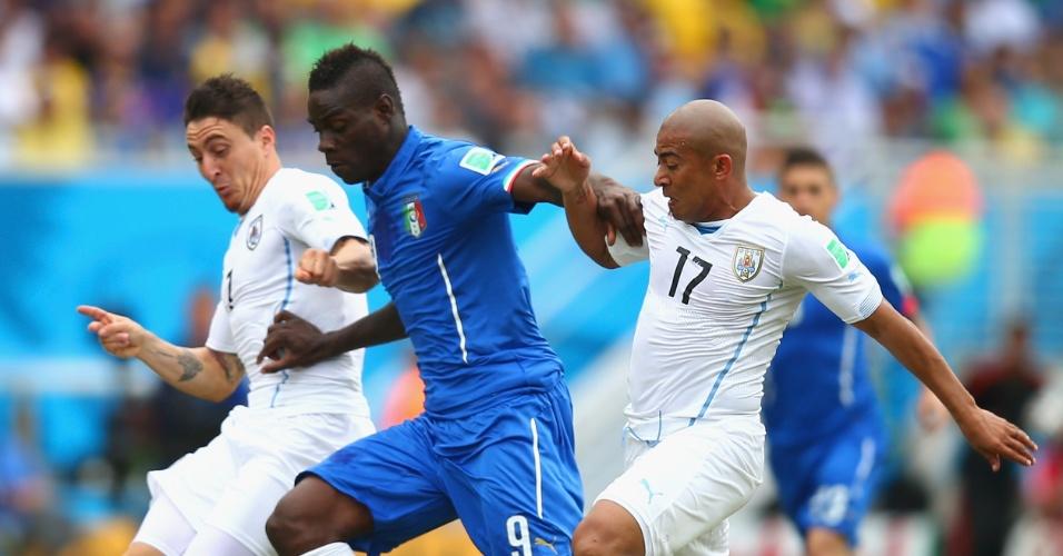 Mario Balotelli briga para escapar da marcação dos uruguaios Cristian Rodriguez e Egidio Arevalo Rios - 24/06/2014