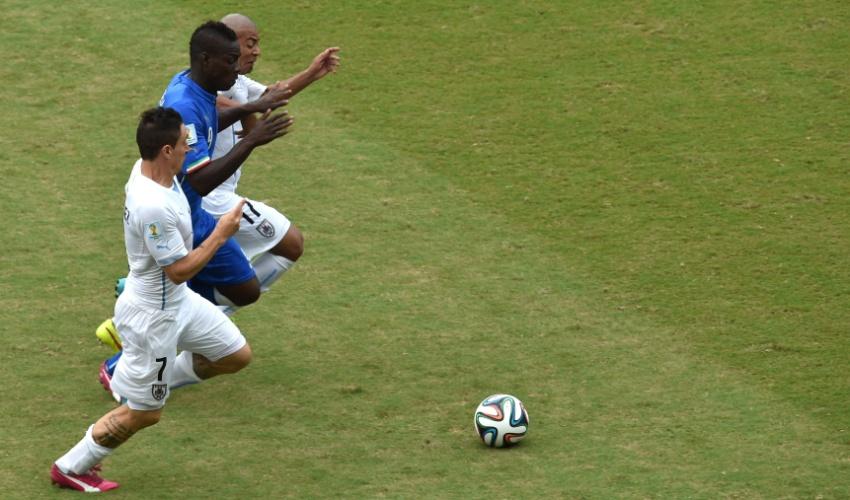 Mario Balotelli, da Itália, disputa bola com Cristian Rodriguez e Arevalo Rios, do Uruguai, em partida na Arena das Dunas