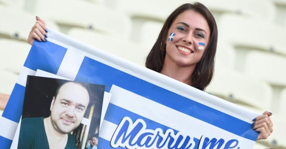 Mulher segura cartaz com pedido de casamento no Castelão antes do início de Grécia e Costa do Marfim