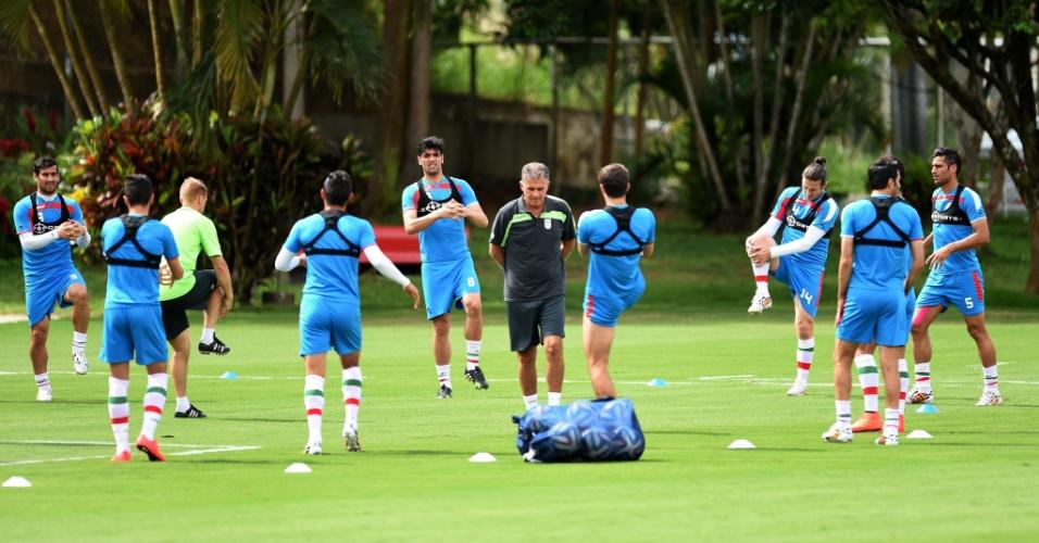 Técnico português Carlos Queiroz caminha pelo gramado do Barradão enquanto os jogadores do Irã realizam exercícios físicos. Seleção encara a Bósnia nesta quarta-feira, na Fonte Nova