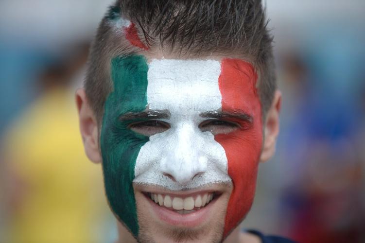Torcedor da Itália pinta o rosto com as cores da bandeira do país, na Arena das Dunas