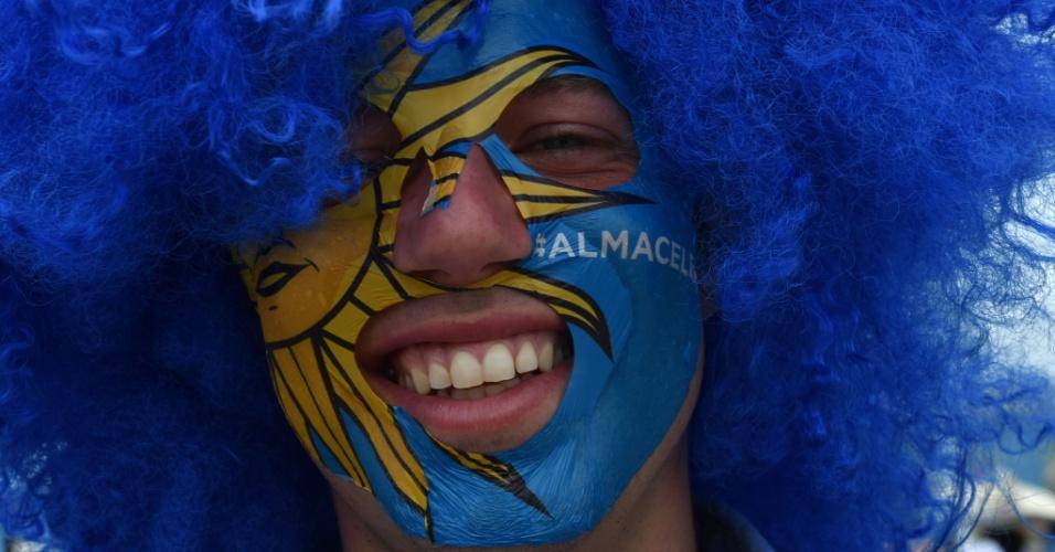 Torcedor exibe máscara com a bandeira uruguaia durante jogo contra a Itália