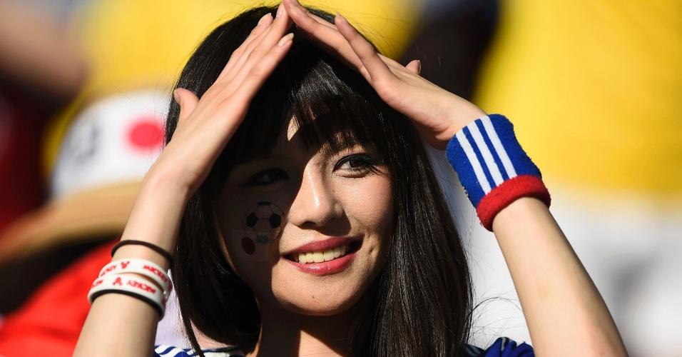 Torcedora japonesa forma sombra no rosto para assistir ao jogo contra a Colômbia