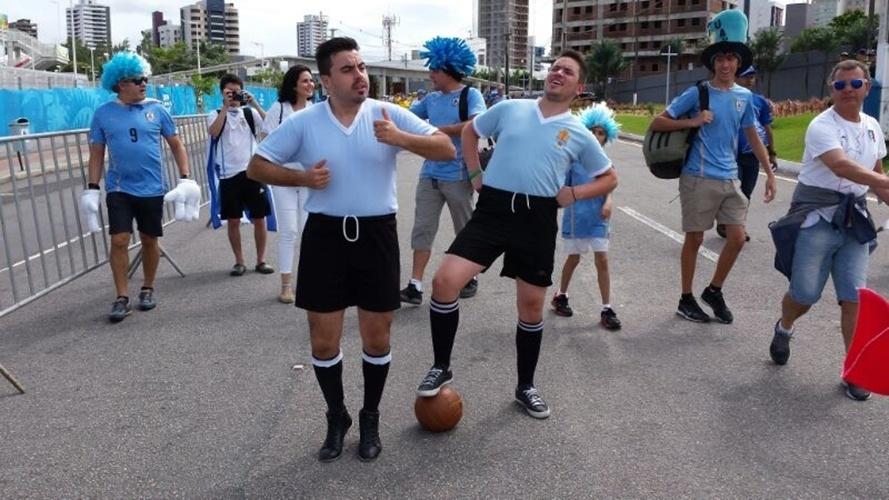 Torcedores uruguaios vestidos com uniformes antigos do lado de fora da Arena das Dunas