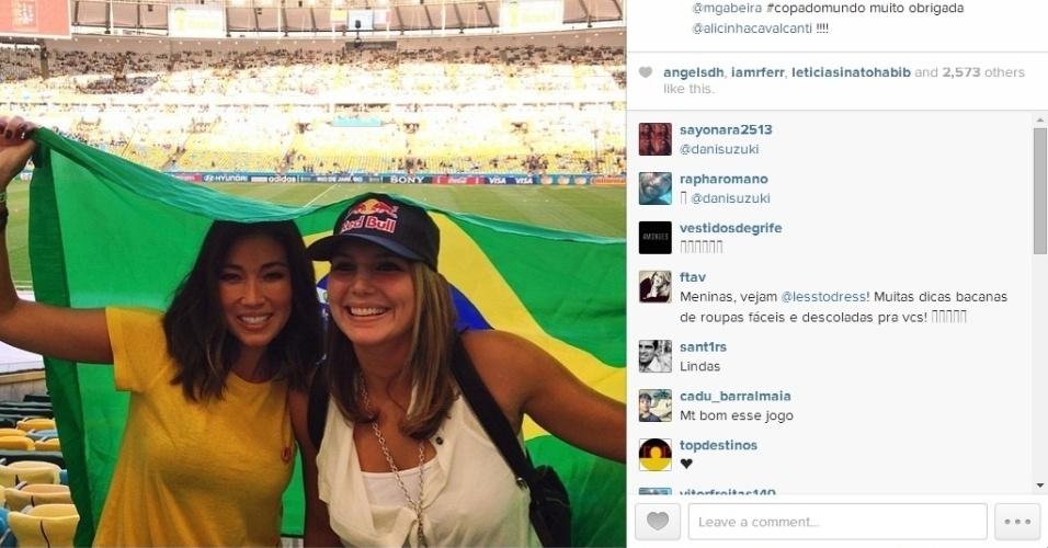 25.jun.2014 - Daniele Suzuki e Maia Gabeira levam bandeira do Brasil ao Maracanã para assistir ao jogo entre França e Equador