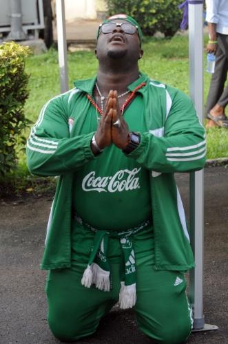 25.jun.2014 - Em Lagos, capital nigeriana, torcedor faz oração durante partida contra a Argentina pela Copa do Mundo