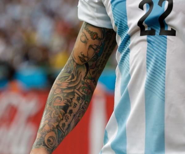 Ezequiel Lavezzi, da Argentina, mostra os desenhos que carrega no braço durante o jogo contra a Nigéria