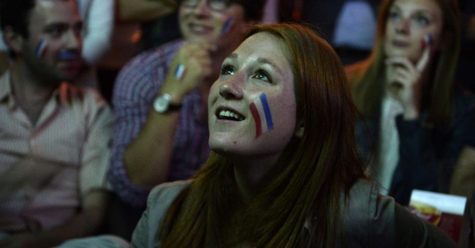 Franceses pintam o rosto com a bandeira do país para acompanhar jogo contra o Equador em bar de Paris