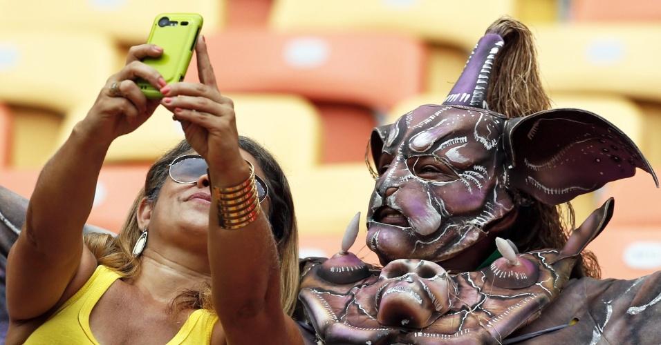 Mulher tira foto com homem usando fantasia na Arena Amazônia antes da partida entre Suiça e Honduras