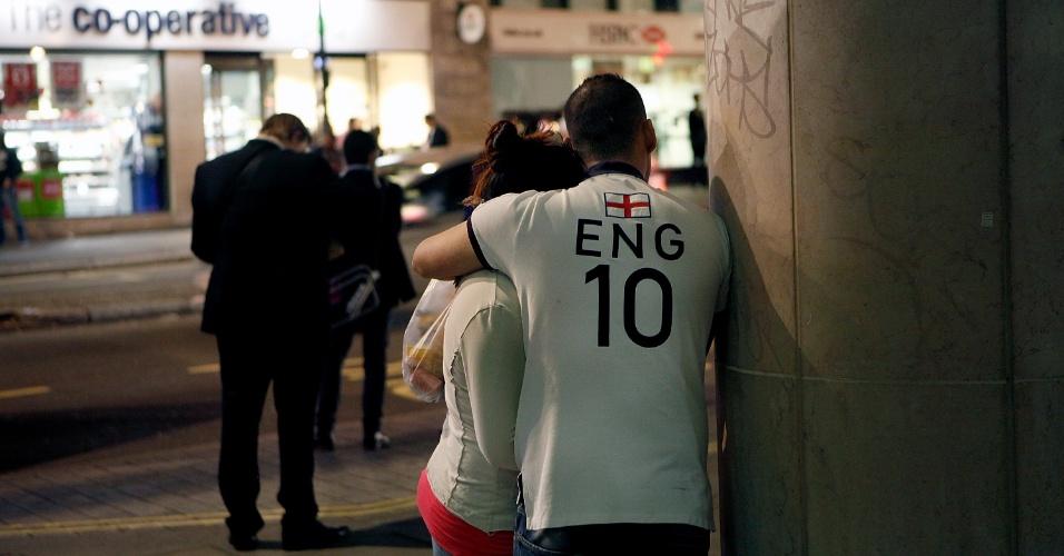 Torcedores se consolam na saída de um pub após jogo de estreia, em que a Inglaterra perdeu para a Itália