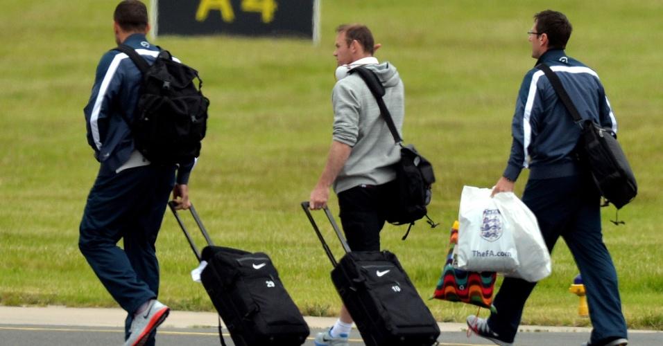 Wayne Rooney chega ao aeroporto de Manchester com a delegação inglesa após eliminação precoce na Copa do Mundo