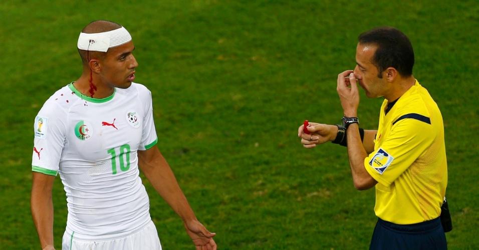 Árbitro pede para o argelino Sofiane Feghouli deixar o campo após continuar com a cabeça sangrando no jogo contra a Rússia