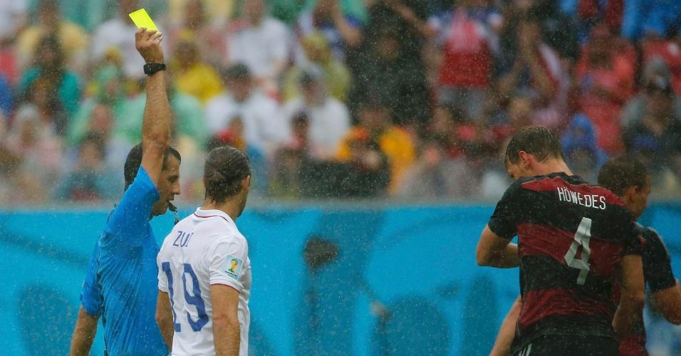 26.jun.2014 - Árbitro Ravshan Irmatov mostra o cartão amarelo para o alemão Höwedes, contra os EUA, na Arena Pernambuco