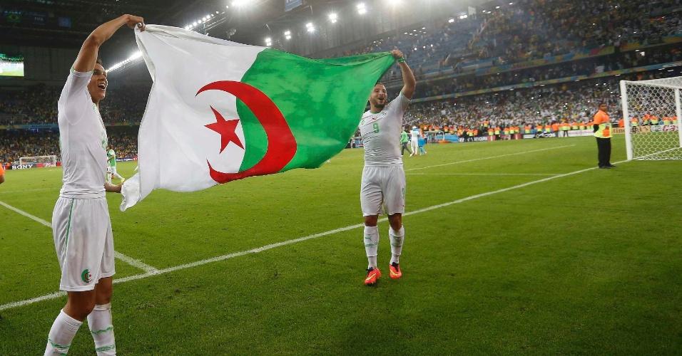 Argelinos Aissa Mandi e Nabil Ghilas exibem orgulhosos a bandeira do país após a classificação para as oitavas de final da Copa
