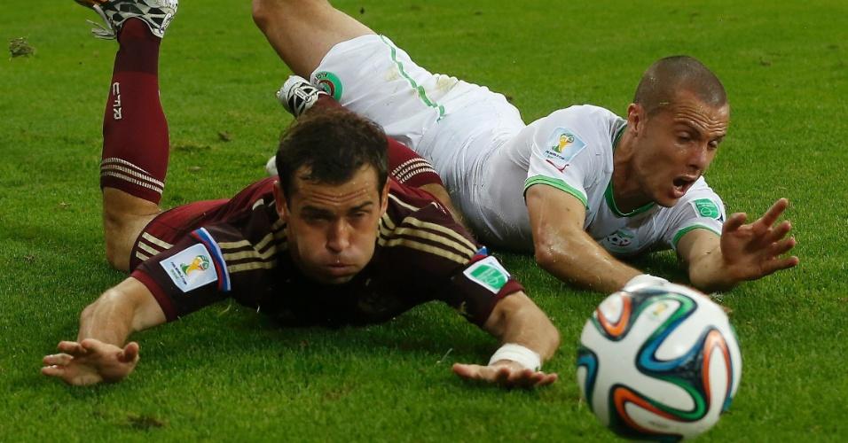 Djamel Mesbah, da Argélia, desliza no gramado da Arena da Baixada ao lado de Alexander Kerzhakov, da Rússia