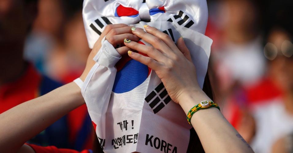 Em Seul, torcedora sul-coreana esconde o rosto com a bandeira do país após eliminação da seleção na primeira fase da Copa do Mundo