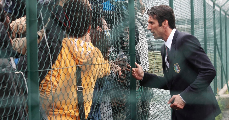 Gianluigi Buffon (dir.) conversa com torcedores após desembarque da delegação italiana em Milão