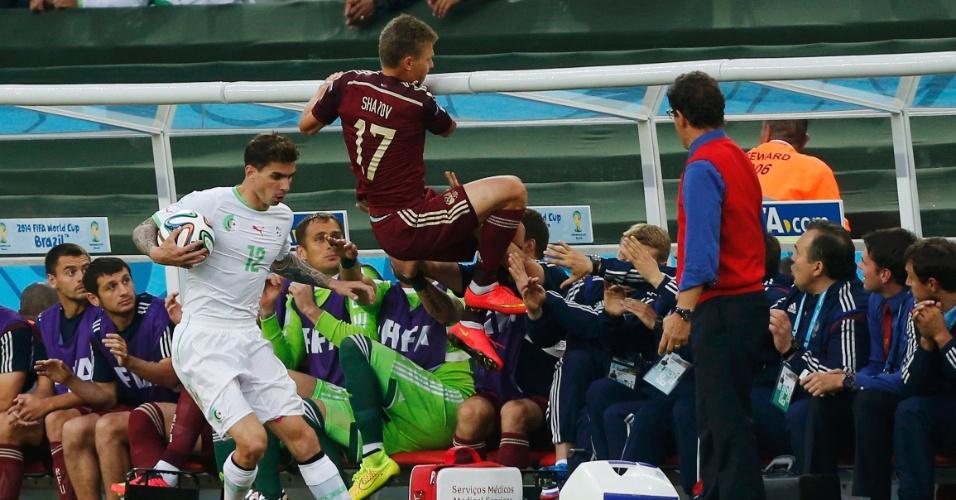 Oleg Shatov, da Rússia, se segura no banco de reservas após se descontrolar em lance contra a Argélia, na Arena da Baixada