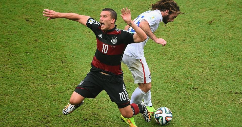26.jun.2014 - Podolski, da Alemanha, é derrubado após perder a bola para Kyle Beckerman, dos EUA, na Arena Pernambuco