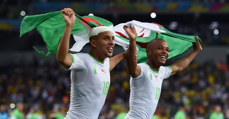 Sofiane Feghouli (esq) e Yacine Brahimi carregam bandeiras da Argélia para comemorar a classificação para as oitavas de final da Copa, depois de empatar com a Rússia