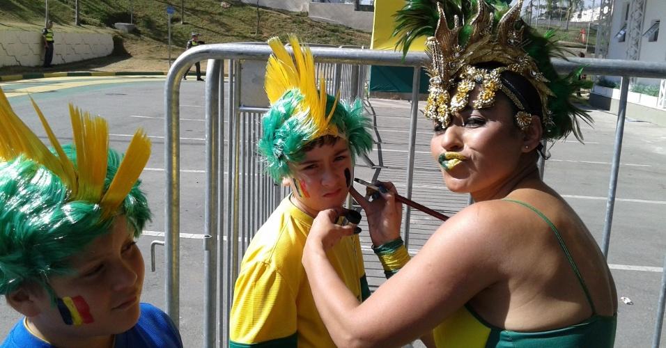 Torcedora pinta o rosto do filho antes do jogo entre Coreia do Sul e Bélgica, no Itaquerão