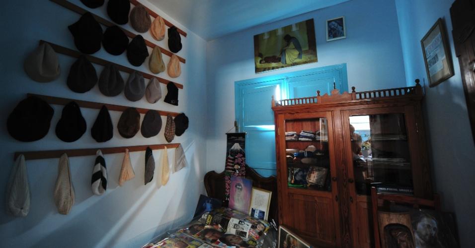 A paixão do médium por boinas é exibida em uma parede com uma variedade delas