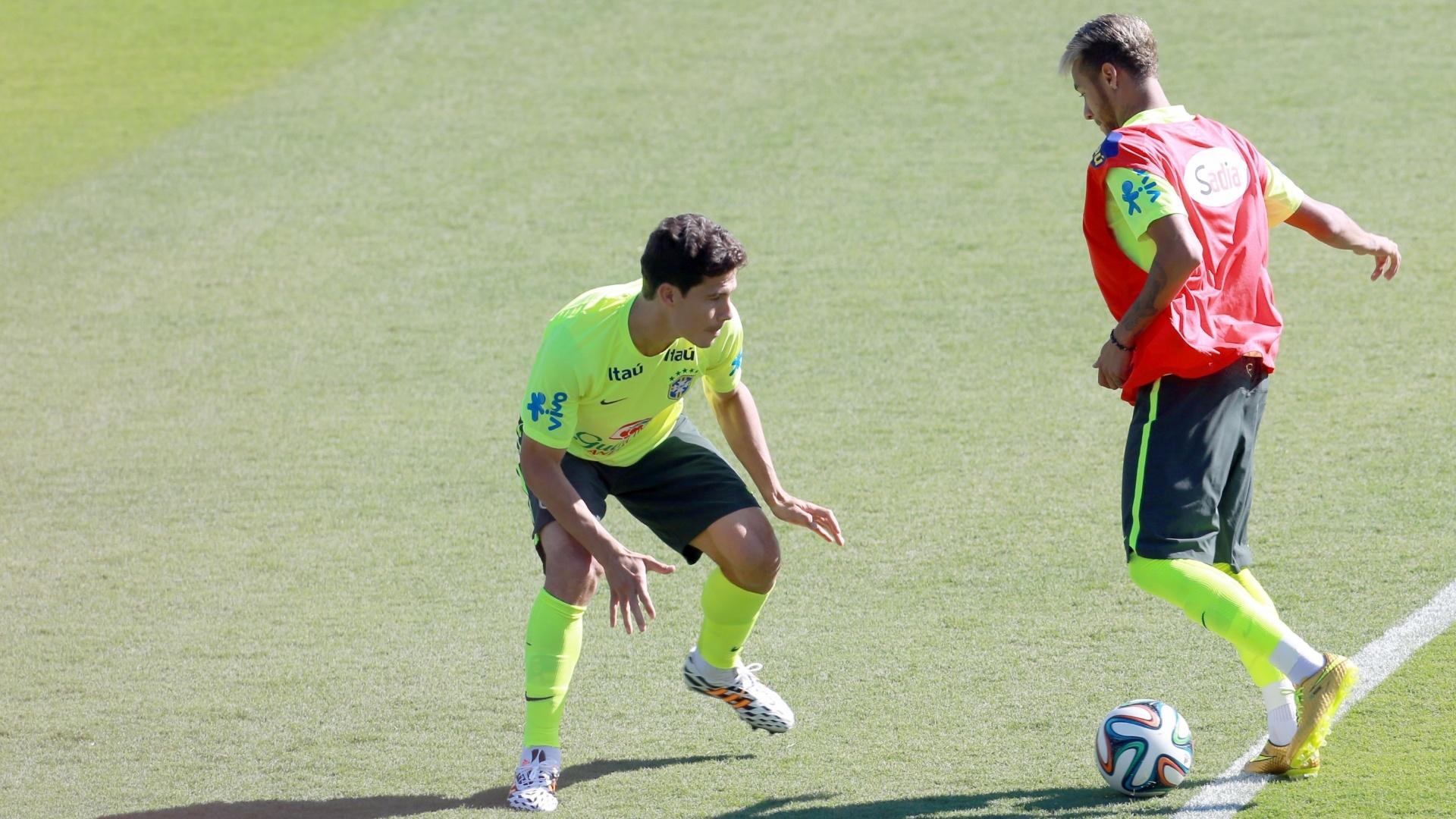 27.jun.2014 - Hernanes marca Neymar durante 'rachão' no treino da seleção brasileira no Sesc Venda Nova, em Belo Horizonte