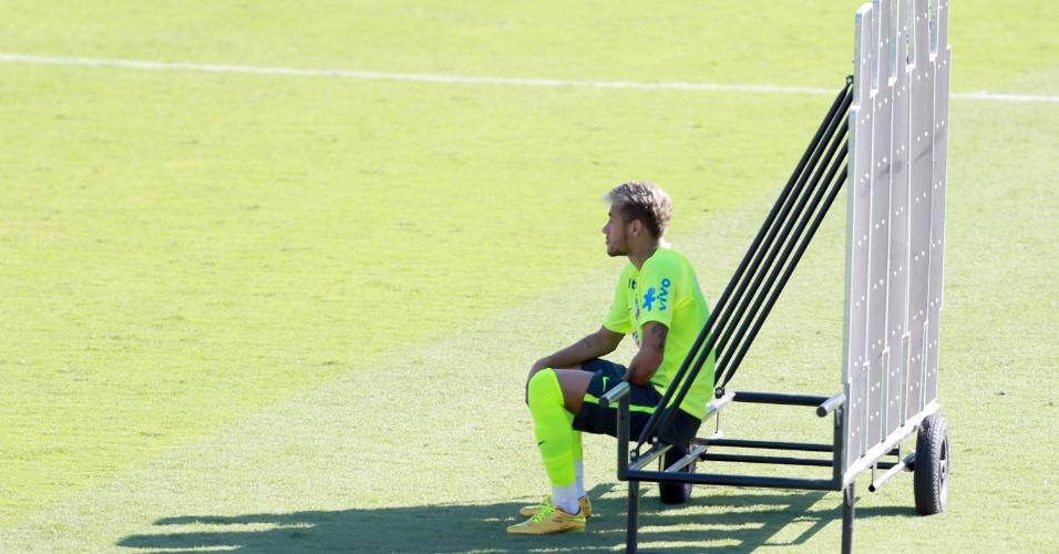 27.jun.2014 - Neymar senta em barreira de bonecos para descansar durante treino da seleção brasileira