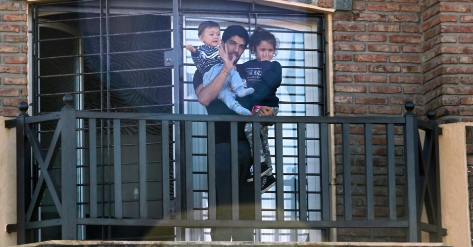 Luis Suárez acena para os fãs da janela da casa da mãe do jogador, no Uruguai. O jogador apareceu na janela junto aos filhos Benjamin e Delfina