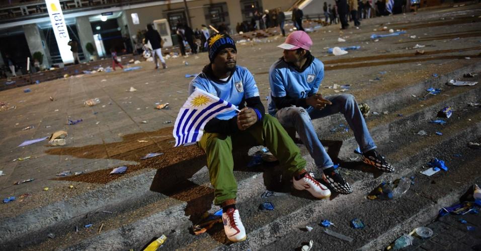 28.jun.2014 - Amigos uruguaios sentam em escada no centro de Montevidéu após eliminação da seleção na Copa do Mundo