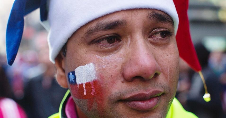 28.jun.2014 - Em Santiago, lágrimas escorrem sobre bandeira chilena no rosto de torcedor após eliminação nos pênaltis