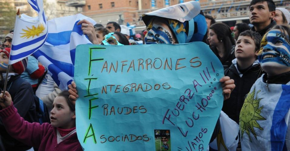 28.jun.2014 - Torcedor uruguaio leva cartaz com crítica à Fifa para praça em Montevidéu enquanto assiste jogo contra a Colômbia