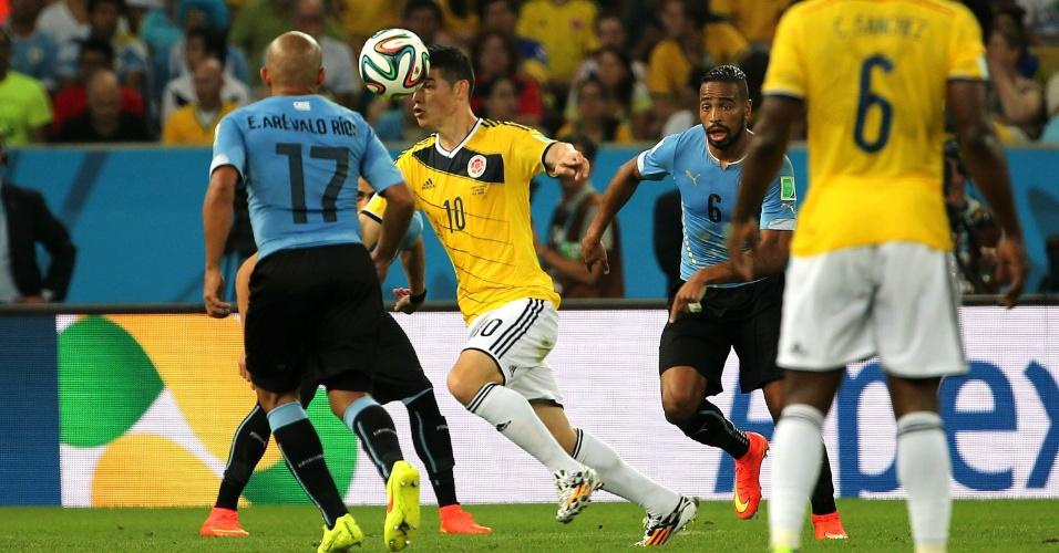 Colombiano James Rodríguez tenta escapar da marcação de uruguaios durante jogo pelas oitavas de final