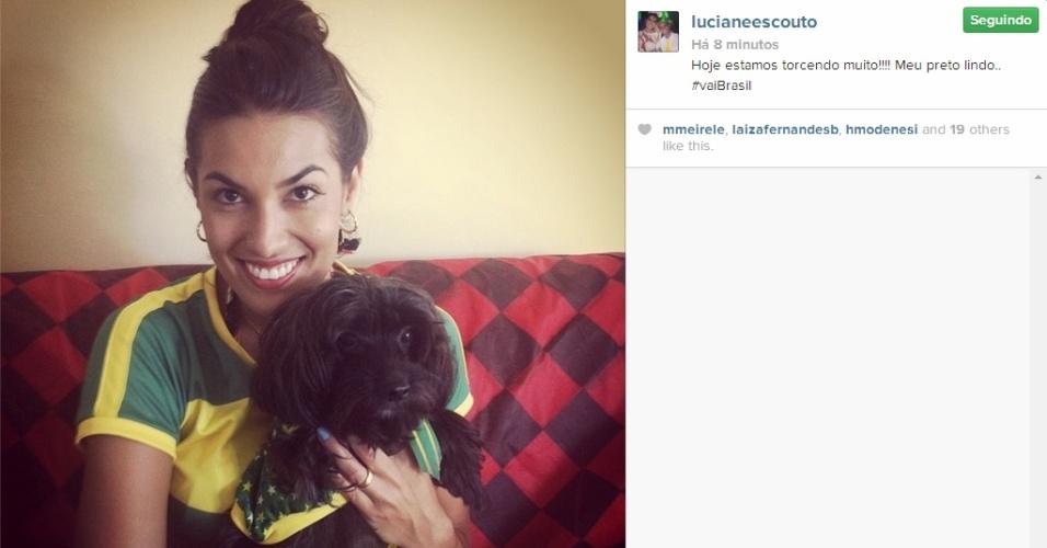 Com seu cachorro, a musa do vôlei Luciane Escouto acompanha de sua casa a partida entre Brasil x Chile
