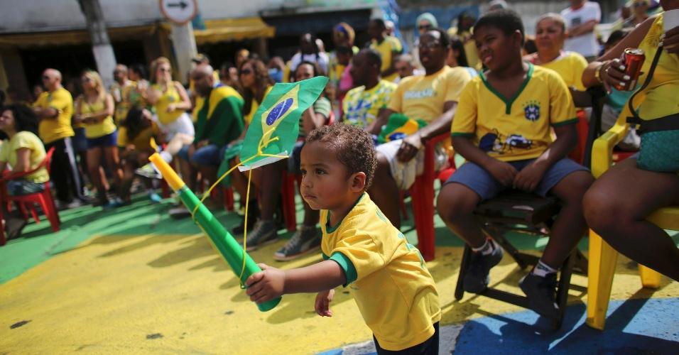 Criança brinca enquanto os torcedores assistem ao jogo entre Brasil e Chile no bairro do Bixiga, em São Paulo