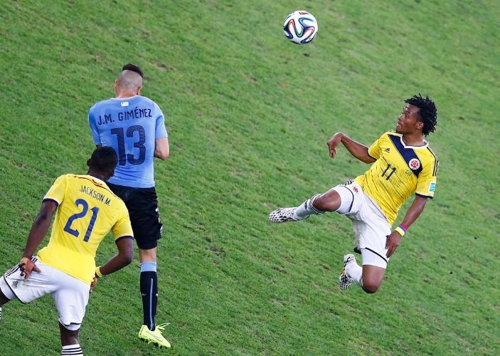 Cuadrado, da Colômbia, sobe para disputar bola com defesa do Uruguai