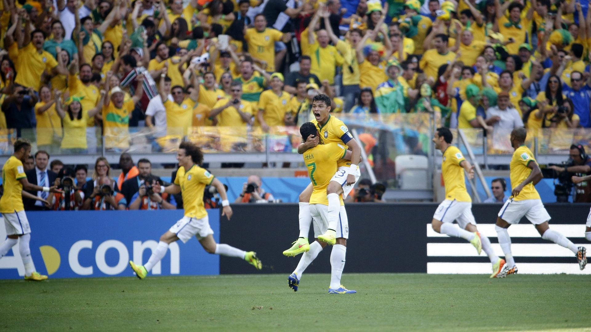 David Luiz, ao fundo, comemora o primeiro gol brasileiro, enquanto Thiago Silva é carregado por Hulk