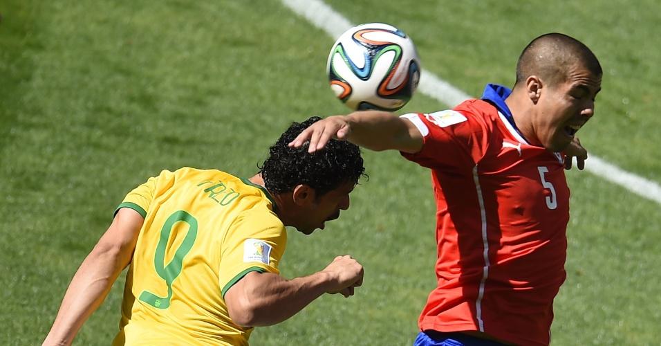 Fred disputa a bola no alto com Francisco Silva, do Chile, no primeiro tempo de jogo no Mineirão