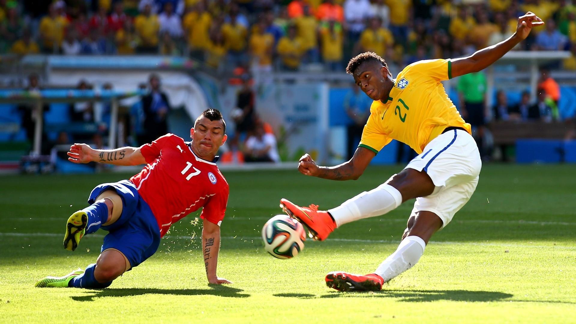 Jô tenta o chute, marcado de perto por Medel durante as oitavas de final contra o Chile