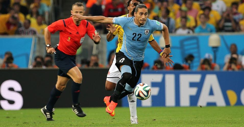 Martín Cárceres corre com a bola dominada durante jogo entre Uruguai e Colômbia pelas oitavas de final da Copa