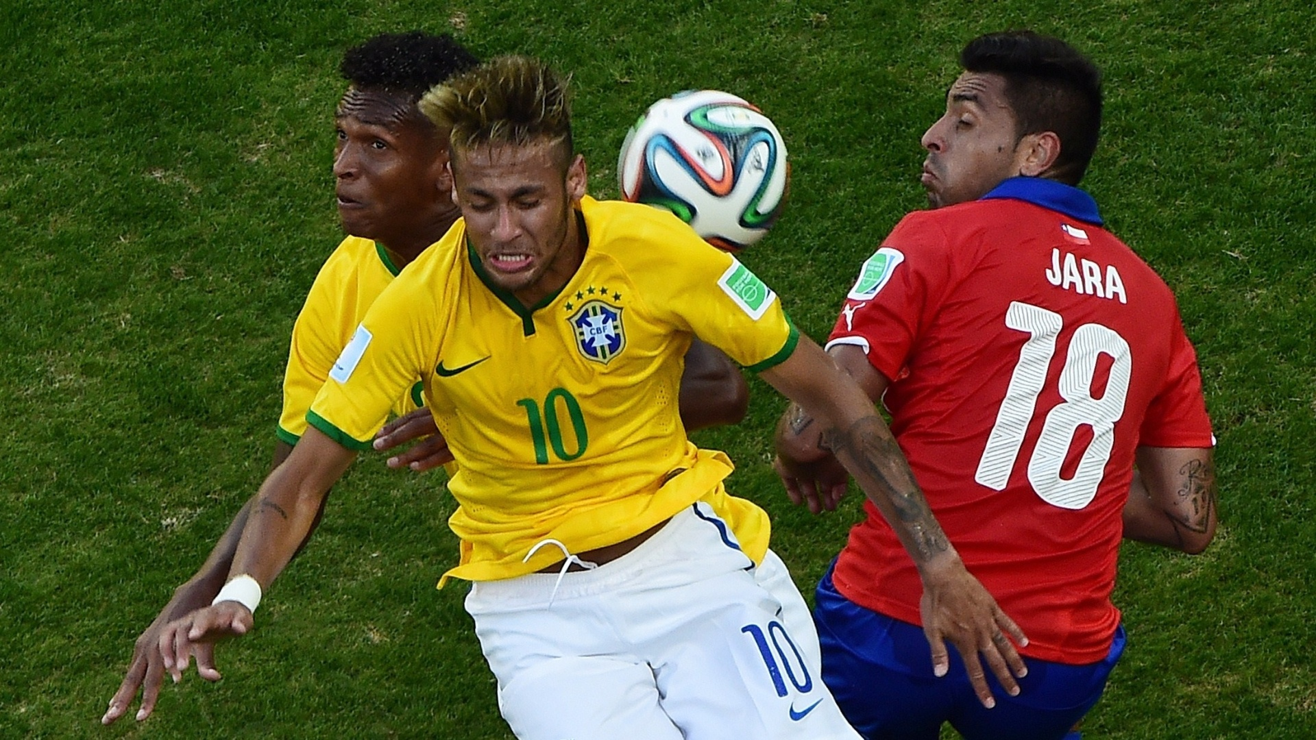 Neymar e Jô dividem a mesma bola na partida contra o Chile, no Mineirão