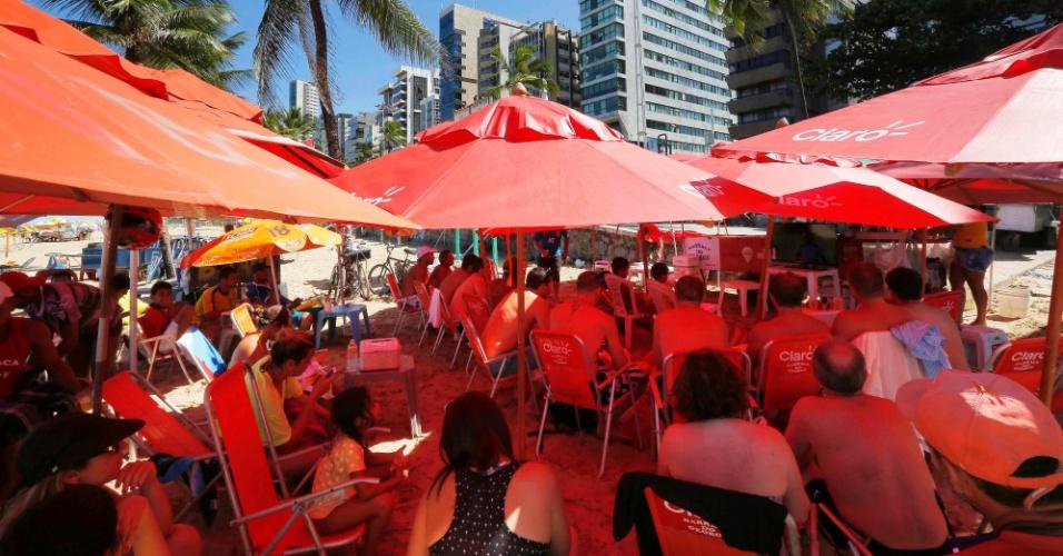 Pessoas acompanham a partida entre Brasil e Chile de uma praia em Recife